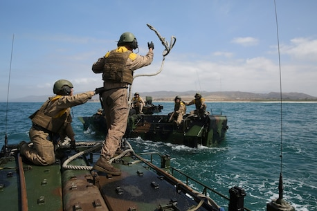"Marines with Amphibious Assault Vehicle Platoon, Company B, Ground Combat Element Integrated Task Force, throw a rope from an AAV, to a ""disabled"" AAV, in the Pacific Ocean during a Marine Corps Operational Test and Evaluation Activity assessment May 12, 2015, near Red Beach training area, aboard Marine Corps Base Camp Pendleton, California. The GCEITF AAV Platoon is executing the final phase of their Marine Corps Operational Test and Evaluation Activity assessment by conducting beach and water-borne tasks. From October 2014 to July 2015, the GCEITF will conduct individual and collective level skills training in designated ground combat arms occupational specialties in order to facilitate the standards-based assessment of the physical performance of Marines in a simulated operating environment performing specific ground combat arms tasks. (U.S. Marine Corps photo By Gunnery Sgt. Matt Epright/Released)"