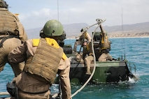"""Marines with Amphibious Assault Vehicle Platoon, Company B, Ground Combat Element Integrated Task Force, catch a rope from an AAV, to attach to their """"disabled"""" AAV, in the Pacific Ocean during a Marine Corps Operational Test and Evaluation Activity assessment May 12, 2015, near Red Beach training area, aboard Marine Corps Base Camp Pendleton, California. The GCEITF AAV Platoon is executing the final phase of their Marine Corps Operational Test and Evaluation Activity assessment by conducting beach and water-borne tasks. From October 2014 to July 2015, the GCEITF will conduct individual and collective level skills training in designated ground combat arms occupational specialties in order to facilitate the standards-based assessment of the physical performance of Marines in a simulated operating environment performing specific ground combat arms tasks. (U.S. Marine Corps photo By Gunnery Sgt. Matt Epright/Released)"""
