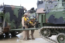 Cpl. Darin Bean, left, and Lance Cpl. Nicholas Cascone, both amphibious assault vehicle crewmen with AAV Platoon, Company B, Ground Combat Element Integrated Task Force, attach a tow-bar to an AAV during a pilot test May 9, 2015, at Red Beach training area, aboard Camp Pendleton, California. The GCEITF AAV Platoon is executing the final phase of their Marine Corps Operational Test and Evaluation Activity assessment by conducting beach and water-borne tasks. From October 2014 to July 2015, the GCEITF will conduct individual and collective level skills training in designated ground combat arms occupational specialties in order to facilitate the standards-based assessment of the physical performance of Marines in a simulated operating environment performing specific ground combat arms tasks. (U.S. Marine Corps photo By Gunnery Sgt. Matt Epright/Released)