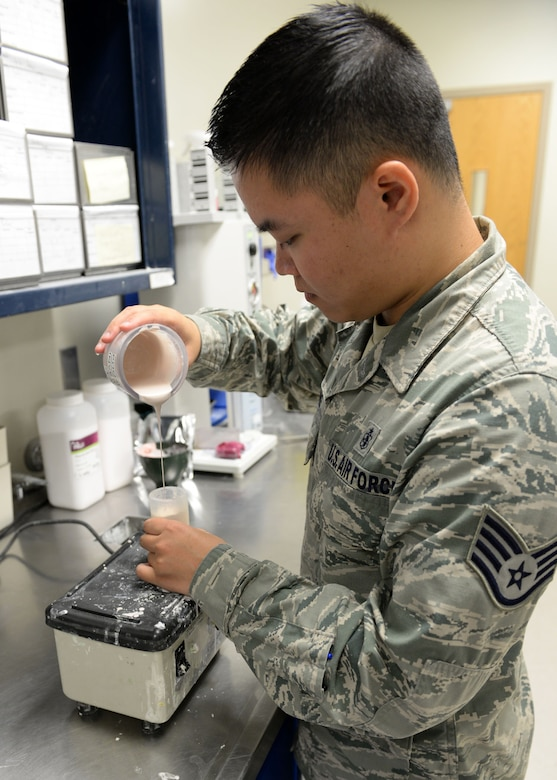 Staff Sgt. Yuxiong Liang, 36th Medical Operations Squadron dental lab technician, pours investment, or liquid stone, at a slow pace to let air out to ensure bubbles aren't trapped in a final crown mold May 11, 2015, at Andersen Air Force Base, Guam. The dental clinic here consists of three elements – support, clinical and a dental lab. (U.S. Air Force photo by Airman 1st Class Joshua Smoot/Released)