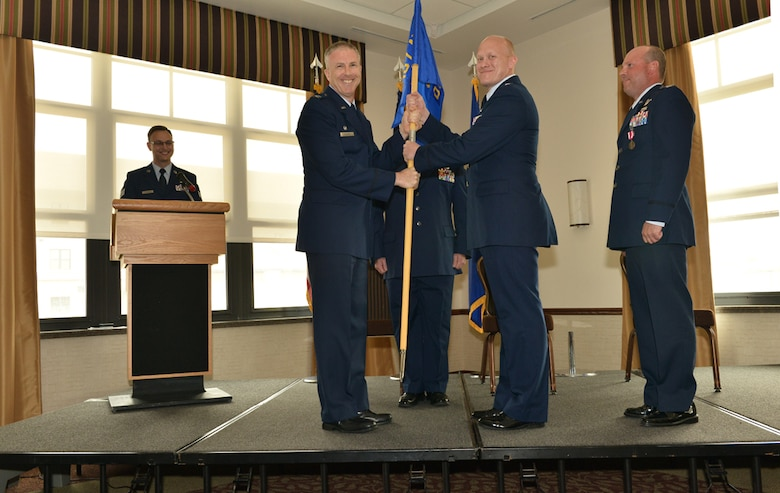 107th AW Commander Col. Robert G. Kilgore presents the 107th AW Operations Group flag to new commander, Lt. Col. Gary R. Charlton II, during a change of command ceremony at the Niagara Falls Air Reserve Station, May 16, 2015.