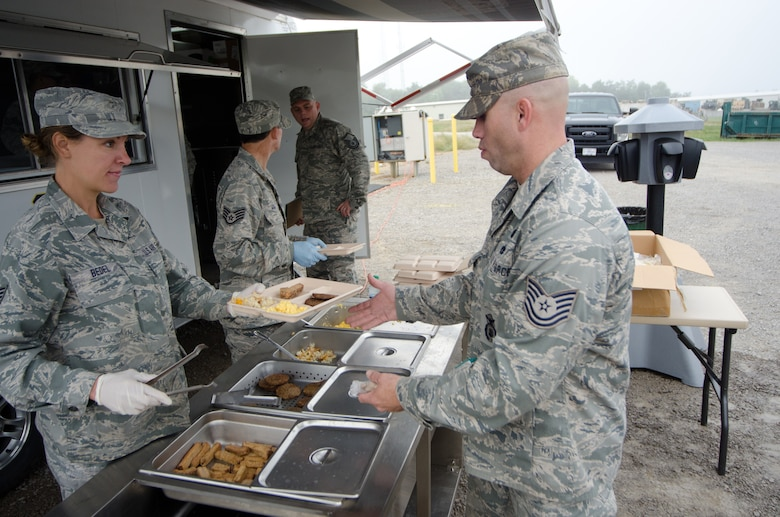Tech. Sgt. Amanda Bedel, a food services specialist from the Kentucky Air National Guard's 123rd Force Support Squadron, serves breakfast to Tech. Sgt. George Whelan, a combat arms instructor in the 123rd Security Forces Squadron, at the Wendell H. Ford Regional Training Center in Greenville, Ky., on Sept. 17, 2014. The Force Support Squadron prepared hot meals for the security forces Airmen during a five-day field training exercise. (U.S. Air National Guard photo by Master Sgt. Phil Speck)