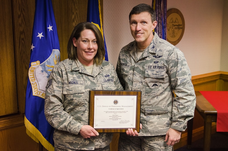 Col. Jeff Wilkinson, vice commander of the 123rd Airlift Wing, presents a certificate of recognition to Staff Sgt. Windy Wagner, chief of information protection, at the Kentucky Air National Guard Base in Louisville, Ky., Jan 8, 2015. Wagner was recognized for providing outstanding support to the U.S. Office of Personnel Management in its execution of security clearance investigations. (U.S. Air National Guard photo by Master Sgt. Phil Speck)