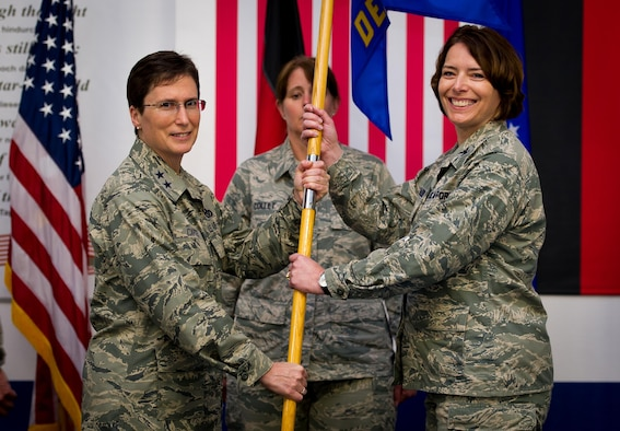 Maj. Gen. Theresa Carter, the Air Force Installation and Mission Support Center commander, passes the AFIMSC Detachment 4 flag to Col. Andra Clapsaddle, the AFIMSC Detachment 4 commander, during an assumption of command ceremony May 15, 2015, at Ramstein Air Base, Germany. AFIMSC is establishing detachments at each major command in order to best support the needs the management and operation of its installations while leveraging centralized capabilities in the AFIMSC headquarters, its six primary subordinate units and two direct reporting units (U.S. Air Force photo/Tech. Sgt. Ryan Crane)