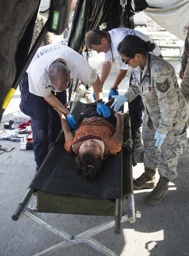An Airman with Joint Task Force-505, along with rescue and medical personnel, provide aid to an earthquake victim at a medical triage area at Tribhuvan International Airport, Kathmandu, Nepal, after a 7.3 magnitude-earthquake struck the country, May 12, 2015. JTF-505, along with other multinational forces and humanitarian relief organizations have been providing aid after a 7.8-magnitude earthquake struck the country, April 25. At Nepal's request the U.S. government ordered JTF-505 to provide unique capabilities to assist Nepal. (U.S. Marine Corps photo/Staff Sgt. Jeffrey D. Anderson)
