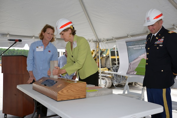 Linda Adcock (Left), U.S. Army Corps of Engineers Nashville District Center Hill Dam Safety project manager assists Tennessee State Rep. Terri Lynn Weaver place a ceremonial concrete form into a small-scale model commemorating the completion of the Center Hill Dam Barrier Wall Project May 18, 2015 on the work platform of the dam.