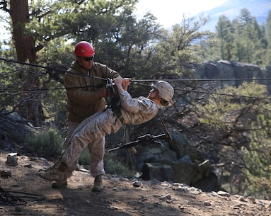 Staff Sgt. Raphael Palisoc, mountain leader, secures Sgt. Rebecca Rutherford, mortar man, Weapons Company, Ground Combat Element Integrated Task Force, onto a rope bridge during the final Marine Corps Operational Test and Evaluation Activity assessment aboard Marine Corps Mountain Warfare Training Center Bridgeport, California, May 18, 2015. From October 2014 to July 2015, the GCEITF will conduct individual and collective level skills training in designated ground combat arms occupational specialties in order to facilitate the standards-based assessment of the physical performance of Marines in a simulated operating environment performing specific ground combat arms tasks. (U.S. Marine Corps photo by Cpl. Paul S. Martinez/Released)