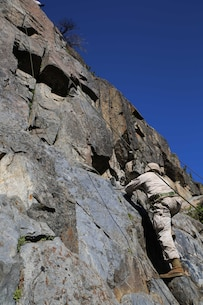 Sgt. Randy Myers, rifleman, Company A, Ground Combat Element Integrated Task Force, climbs a 40-foot cliff face during the final Marine Corps Operational Test and Evaluation Activity assessment aboard Marine Corps Mountain Warfare Training Center Bridgeport, California, May 18, 2015. From October 2014 to July 2015, the GCEITF will conduct individual and collective level skills training in designated ground combat arms occupational specialties in order to facilitate the standards-based assessment of the physical performance of Marines in a simulated operating environment performing specific ground combat arms tasks. (U.S. Marine Corps photo by Cpl. Paul S. Martinez/Released)