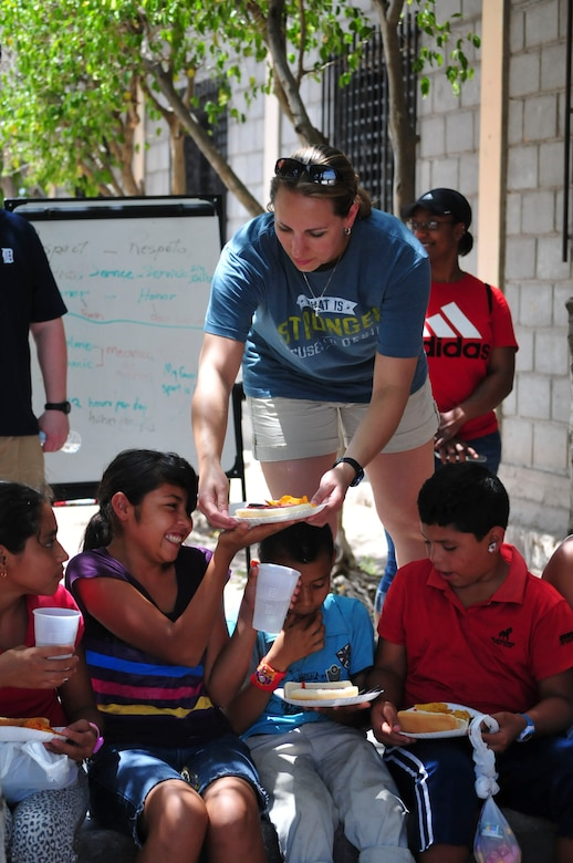 U.S. Air Force Capt. Laura Miller, Joint Task Force-Bravo adjutant, serves food to a group of children from the Saint Anthony of Padua Boys Home, as well as neighborhood children, outside La Paz, Honduras May 16, 2015. The 1st Battalion, 228th Aviation Regiment from Soto Cano Air Base leads monthly visits to local orphanages around Soto Cano Air Base, to serve the community. (U.S. Air Force photo by Capt. Christopher Love)