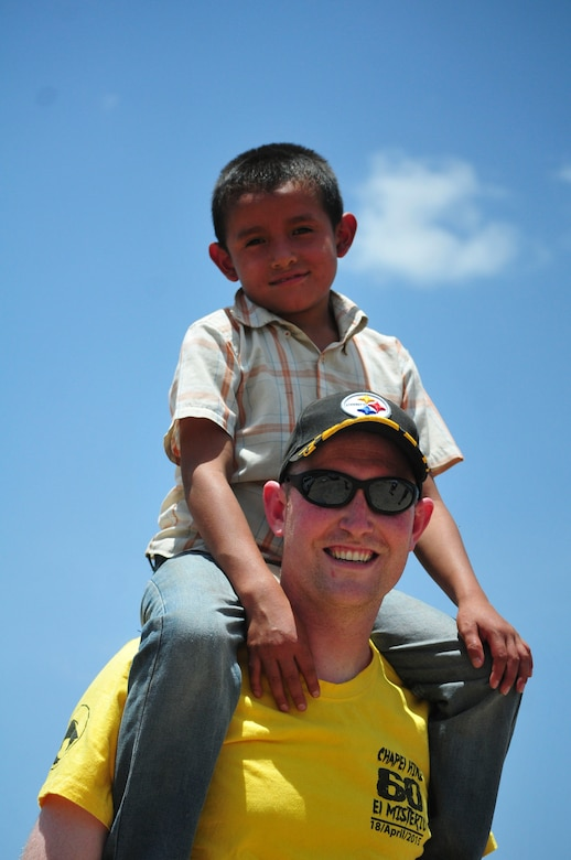 A boy sits on the shoulders of U.S. Air Force First Lieutenant Michael Harrison, Joint Task Force-Bravo logistics director, during the Task Force's visit to the Saint Anthony of Padua Boys Home outside La Paz, Honduras May 16, 2015. The 1st Battalion, 228th Aviation Regiment from Soto Cano Air Base visits to local orphanages around Soto Cano Air Base, to serve the community. (U.S. Air Force photo by Capt. Christopher Love)