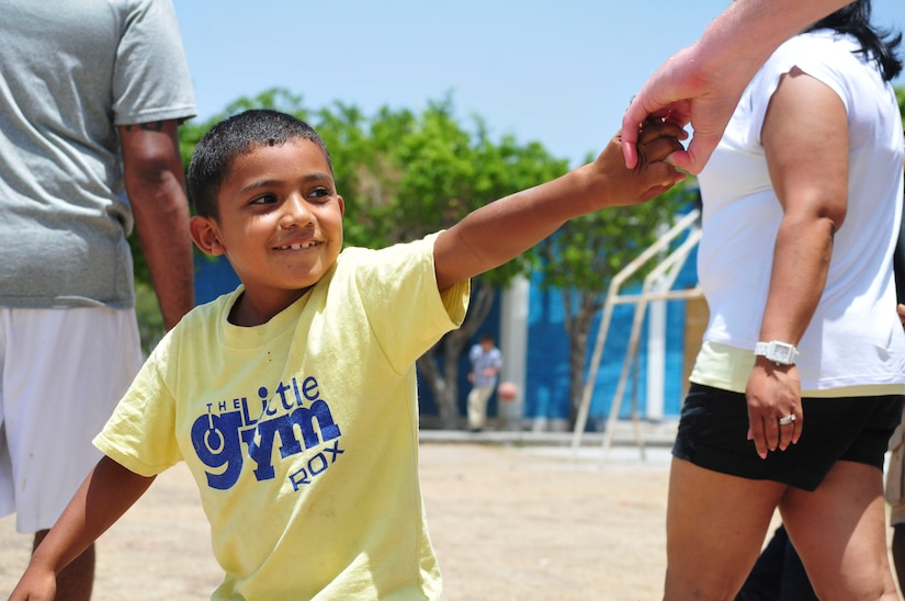 A boy tugs playfully on the hand of a volunteer from Joint Task Force-Bravo during a visit sponsored by the 1st Battalion, 228th Aviation Regiment to the Saint Anthony of Padua Boys Home outside La Paz, Honduras May 16, 2015. The 1-228 leads monthly visits to local orphanages around Soto Cano Air Base, to serve the community. (U.S. Air Force photo by Capt. Christopher Love)