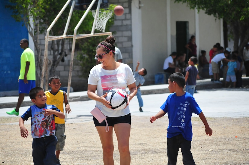 U.S. Army Sgt. Maria Hernandez, 1st Battalion, 228th Aviation Regiment human resources, walks out to a soccer field with a group of boys from the Saint Anthony of Padua Boys Home outside La Paz, Honduras May 16, 2015. The 1-228 leads monthly visits to local orphanages around Soto Cano Air Base, to serve the community. (U.S. Air Force photo by Capt. Christopher Love)