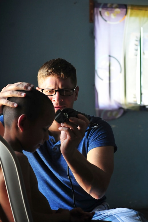 """Chief Warrant Officer Dan Keslar, 1st Battalion, 228th Aviation Regiment CH-47 """"Chinook"""" pilot, gives a haircut to a boy from the Saint Anthony of Padua Boys Home outside La Paz, Honduras May 16, 2015. A regular volunteer, Keslar offers haircuts as part of the 1-228's monthly visits to local orphanages. (U.S. Air Force photo by Capt. Christopher Love)"""