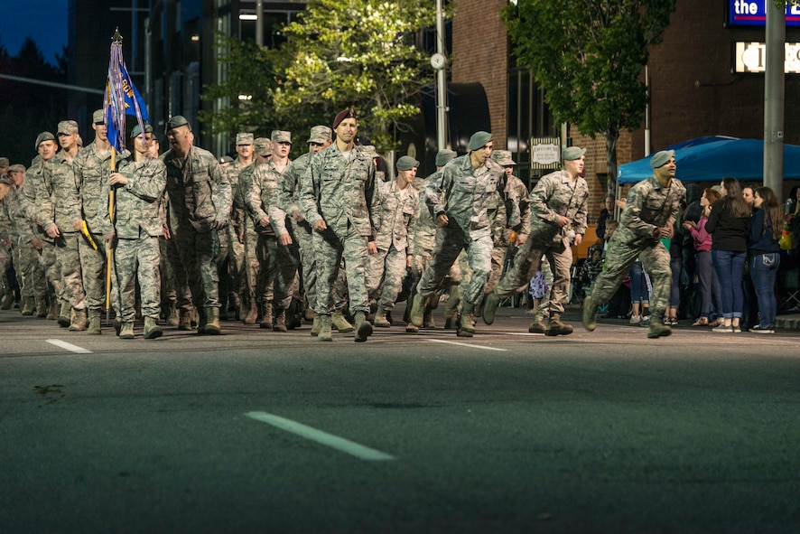 Airmen from the 336th Training Group dash for the crowds in the hunt for some high fives during the 77th Annual Spokane Lilac Festival Armed Forces Torchlight Parade May 16, 2015, in downtown Spokane, Wash. This parade is the largest of its kind in the country and affords attendees a chance to celebrate those who lift up their community and protect its freedom. (U.S. Air Force photo/Staff Sgt. Benjamin W. Stratton)