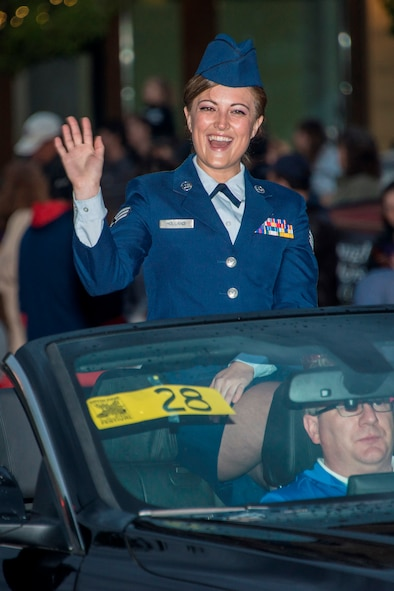 Senior Airman Nicole Holland, 141st Medical Group aerospace medical technician, interacts with crowds during the 77th Annual Spokane Lilac Festival Armed Forces Torchlight Parade May 16, 2015, in downtown Spokane, Wash. Holland was recognized as the Washington Air National Guard Armed Forces Person of the Year, May 14, 2015, at the Davenport Hotel in Spokane, Wash. The Spokane Lilac Festival recognized Spokane military personnel, Fire and Police Department employees and Royalty teachers during the 77th Annual Spokane Lilac Festival Association's All City Civic Military Luncheon. (U.S. Air Force photo/Staff Sgt. Benjamin W. Stratton)