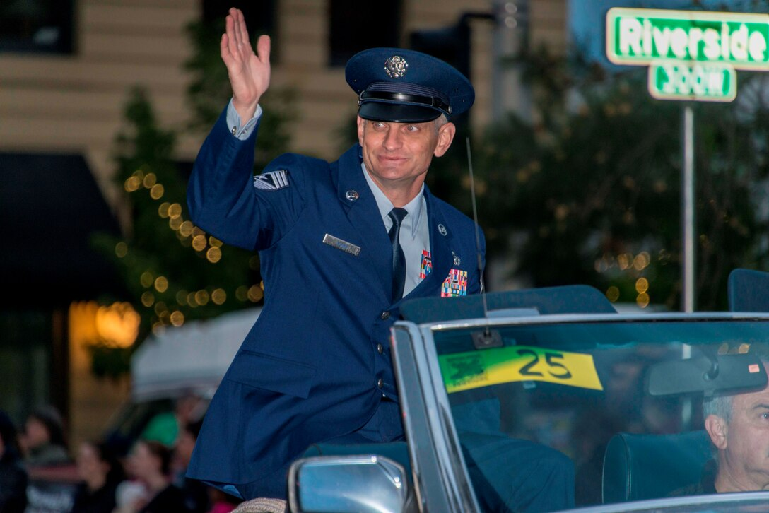 Chief Master Sgt. Christian Pugh, 92nd Air Refueling Wing command chief, waves at crowds from his classic car during the 77th Annual Spokane Lilac Festival Armed Forces Torchlight Parade May 16, 2015, in downtown Spokane, Wash. This parade affords community members an opportunity to remember the sacrifice and service of the nation's military men and women and respect the rich heritage of the Inland Northwest, past and present. (U.S. Air Force photo/Staff Sgt. Benjamin W. Stratton)
