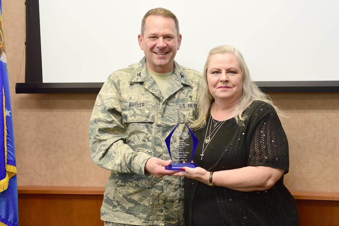 Col. Timothy A. Butler, Air Force Space Command command chaplain, left; awards Debbie Cruz, 460th Space Wing chapel secretary, right; AFSPC Chaplain Core Civilian of the Year May 18, 2015, on Buckley Air Force Base, Colo. The chaplain core civilian of the year award encompasses all civilians that work within the chaplain core. With her victory at the AFSPC level, Cruz will now go on to compete at the Air Force level. (U.S. photo by Airman 1st Class Luke W. Nowakowski/Released)