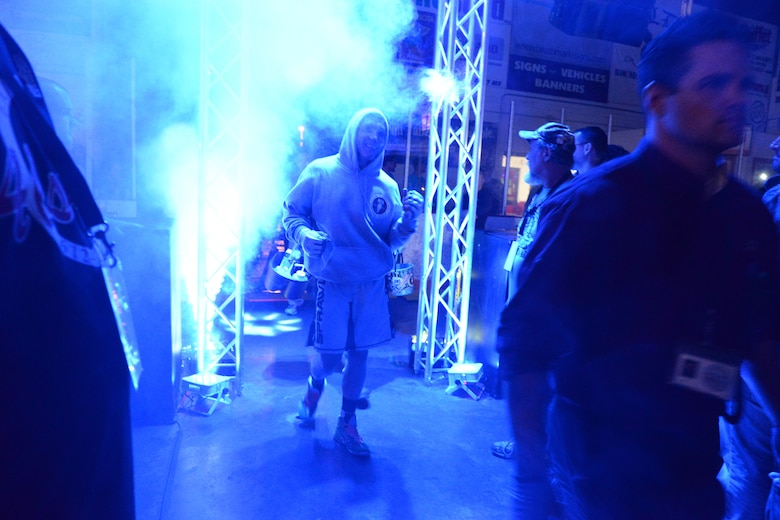 Senior Airman Michael Bullen, of the 119th Security Forces Squadron, makes a s smoky entrance through the dimly lit crowd leading to the center stage fighting cage where he will compete in a mixed martial arts fight at the Freeman Arena, Detroit Lakes, Minnesota, May 16, 2015.  The security forces Airman uses mixed martial arts training and fighting to enhance his fitness and skills to be better prepared in his career field and to be better prepared for potential threats on duty.  (U.S. Air National Guard photo by Senior Master Sgt. David H. Lipp/Released)