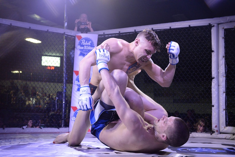 Senior Airman Michael Bullen, of the 119th Security Forces Squadron, top, throws a downward hammer-punch toward his opponent as he grimaces during his mixed martial arts fight in the center stage fighting cage at the Kent Freeman Arena, Detroit Lakes, Minnesota, May 16, 2015.  The security forces Airman uses mixed martial arts training and fighting to enhance his fitness and skills to be better prepared in his career field and to be better prepared for potential threats on duty.  (U.S. Air National Guard photo by Senior Master Sgt. David H. Lipp/Released)