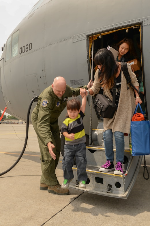 "Master Sgt. Brett Brandemuhl, loadmaster with the 144th Airlift Squadron, Alaska Air National Guard, assists dependents of military members assigned to Osan Air Base, Korea, as they step off at Yokota Air Base, Japan, May 15, 2015. The AANG supported Yokota during a test of the ""total force"" concept, which integrates assets from multiple bases for one mission. (Airman 1st Class Elizabeth Baker/Released)"