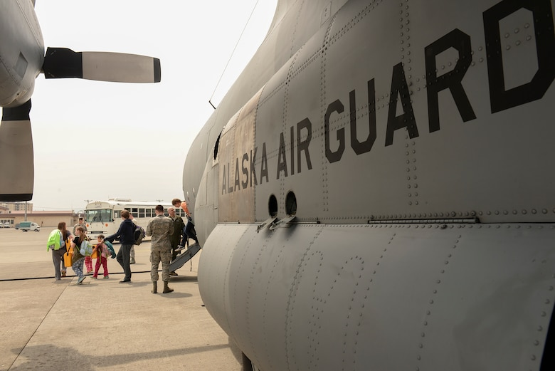An Alaska Air National Guard C-130 Hercules unloads dependents of military members assigned to Osan Air Base, Korea, at Yokota Air Base, Japan, May 15, 2015. Capt. Jason Guinnee, a pilot with the 144th Airlift Squadron, AANG, said that the AANG is always willing and able to assist Yokota and the Pacific region in the event of a disaster. (Airman 1st Class Elizabeth Baker/Released)