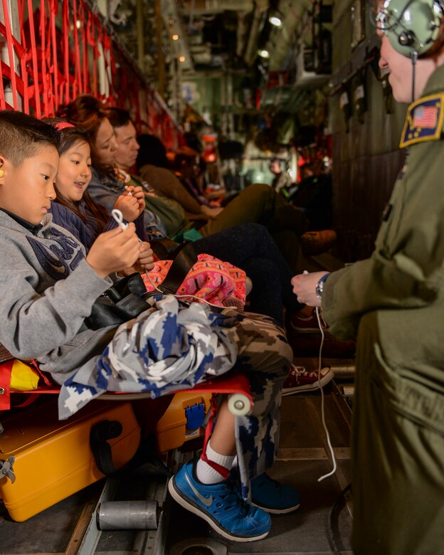 A crew member of a C-130 Hercules entertains military dependents with string tricks during a flight from Osan Air Base, Korea, to Yokota Air Base, Japan, May 15, 2015. The Alaska Air National Guard supported Yokota during a simulated noncombatant evacuation exercise, in part to test Yokota's ability to integrate assets from other bases. (Airman 1st Class Elizabeth Baker/Released)