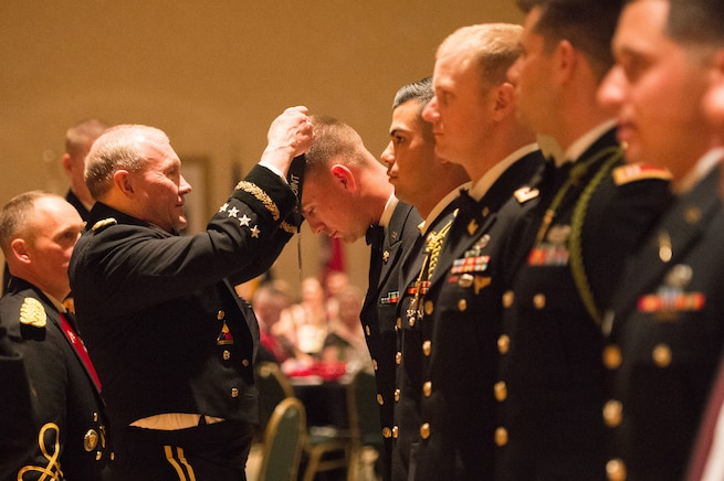 Army Gen. Martin E. Dempsey, chairman of the Joint Chiefs of Staff, presents a soldier with an award for outstanding leadership at the 2nd Armored Brigade Combat Team Ball in Junction City, Kan., May 15, 2015.