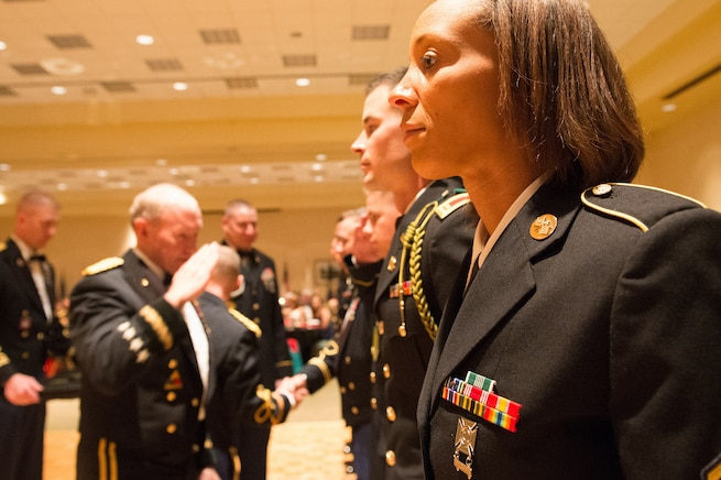 Army Gen. Martin E. Dempsey, chairman of the Joint Chiefs of Staff, salutes after presenting a soldier with an award for outstanding leadership at the 2nd Armored Brigade Combat Team Ball in Junction City, Kan., May 15, 2015.