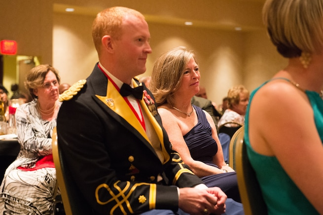 Army Maj. Chris Dempsey and his mother, Deanie Dempsey, listen as Army Gen. Martin E. Dempsey, chairman of the Joint Chiefs of Staff, gives remarks at the 2nd Armored Brigade Combat Team Ball in Junction City, Kan., May 15, 2015.
