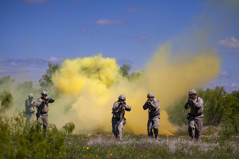 GOODFELLOW AIR FORCE BASE, Texas -- Angelo State University Air Force ROTC Detachment 847 cadets make their way through a cloud of yellow smoke during a field training exercise at a deployed simulation village near Camp Sentinel April 18. The FTX is designed to give cadets a broader understanding of what the Air Force is truly like before committing to serve. (U.S. Air Force photo/ Airman 1st Class Devin Boyer)