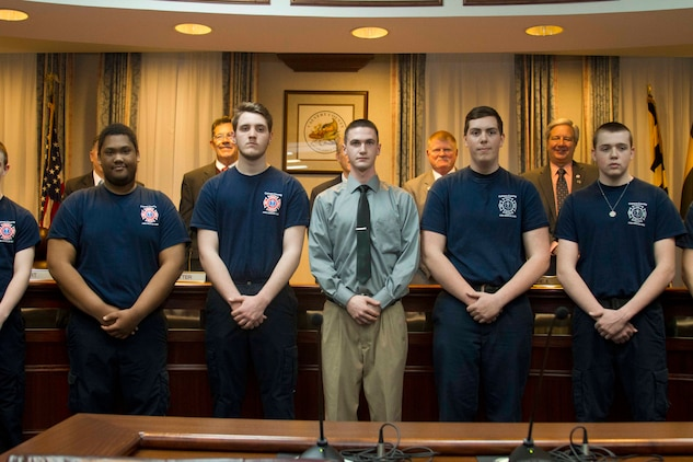 Matthew Shrawder, center, a firefighter with the Dunkirk Volunteer Fire Department, is recognized for his acts of heroism while rescuing a woman from a house fire by the Calvert County Board of Commissioners during their monthly meeting on March 24, 2015. (U.S. Marine Corps photo by Sgt. Bryan Nygaard/Released)