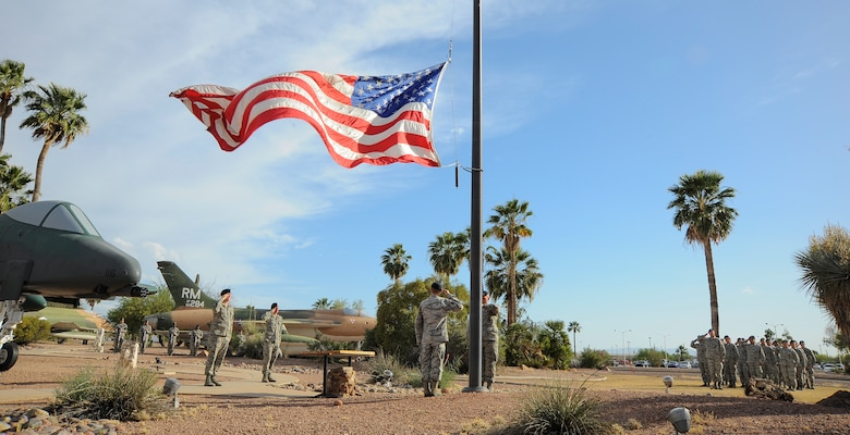 Airmen from the 355th Security Forces Squadron lower the American flag during a retreat ceremony for National Police Week at Davis-Monthan Air Force Base, Ariz., May 14, 2015. The retreat ceremony honored security forces and law enforcement members who have died in the line of duty. (U.S. Air Force photo by Staff Sgt. Angela Ruiz/released)