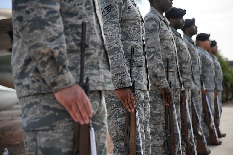 Airmen from the 355th Security Forces Squadron stand with their rifles during a retreat ceremony for National Police Week at Davis-Monthan Air Force Base, Ariz., May 14, 2015. The seven Airmen performed a 3-volley rifle salute for fallen security forces Airmen and fallen law enforcement. (U.S. Air Force photo by Staff Sgt. Angela Ruiz/released)