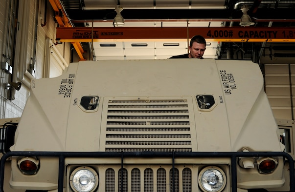 A picture of U.S. Air Force Senior Airman Skylar Marine, a member of the 227th Air Support Operations Squadron, lifting the hood of a High Mobility Multipurpose Wheeled Vehicle.