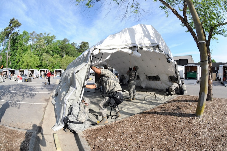 Members of the 113th Wing, D.C. Air National Guard, Fatality Search and Recovery Team put up a tent during Chemical Biological Radiological Nuclear (CBRN) Emergency Response Force Package training, May 14, 2015 in Virginia Beach, Va.  (U.S. Air National Guard photo by Airman 1st Class Anthony Small)