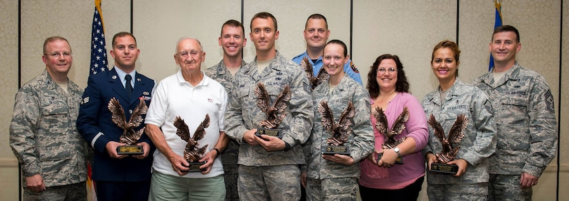 Col. Jeffrey DeVore, Joint Base Charleston commander, and Chief Master Sgt. Mark Bronson, 628th Air Base Wing command chief, pose for a group photo with the award winners during the 628th ABW Quarterly Awards Ceremony May 13, 2015, at the Charleston Club on JB Charleston, S.C. The winners are (left to right) Senior Airman Michael Cassar, Honor Guard Member of the Quarter, Mr. Donald Reed, Volunteer of the Quarter, Capt. James Ferrel, CGO of the Quarter, Tech. Sgt. Kenneth Angel, Noncommissioned Officer of the Quarter, Mr. Jason Frederickson, Cat I Civilian of the Quarter, Airman 1st Class Mariah Magtoto, Airman of the Quarter, Ms. Sandra Walker-Halliman, Cat II Civilian of the Quarter and Master Sgt. Caroline Bunce, SNCO of the Quarter. The Quarterly Awards are held to recognize outstanding Airmen, noncommisioned officers, senior noncomissioned officers, company grade officers and civilians for their hard work and dedication. (U.S. Air Force photo/Airman 1st Class Clayton Cupit)