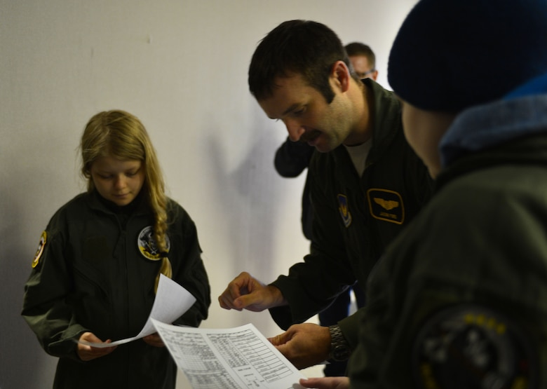 U.S. Air Force Capt. Jason Ford, 871st Air Expeditionary Squadron F-15C Eagle fighter aircraft pilot, gives a simulated mission brief to Arna Tryggvadóttir and Gunnar Guðlaugsson during the Pilot for a Day program at Keflavik International Airport, Iceland, May 13, 2015.The program allowed two terminally ill Icelandic children to experience a day in the life of a U.S. Air Force pilot. (U.S. Air Force photo by 2nd Lt. Meredith Mulvihill/Released)