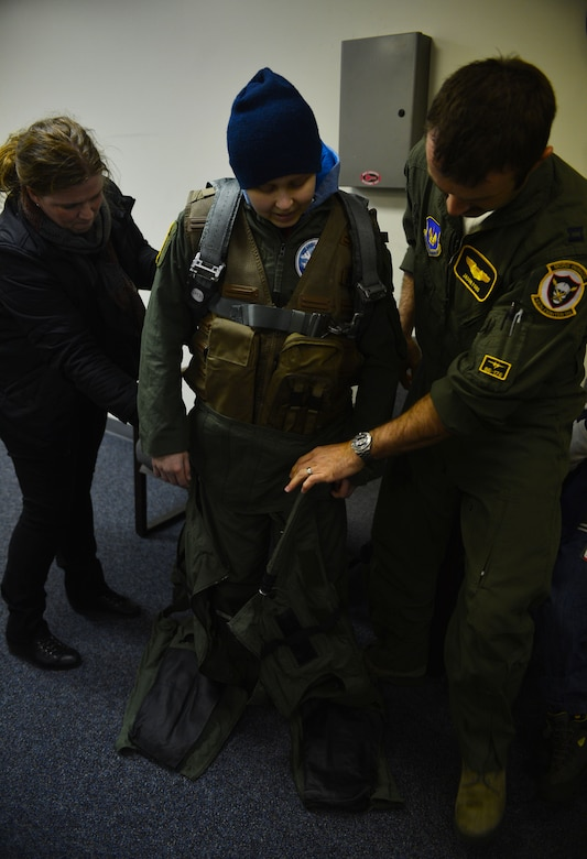U.S. Air Force Capt. Jason Ford, 871st Air Expeditionary Squadron F-15C Eagle fighter aircraft pilot, and Aðalheiður Þorsteinsdóttir, Gunnar Guðlaugsson's mother, help Guðlaugsson don flight equipment during the Pilot for a Day program at Keflavik International Airport, Iceland, May 13, 2015. The 871st AES hosted two children as part of the program,who were fitted with aircrew flight equipment and introduced to what a day in the life of a U.S. Air Force pilot is like. (U.S. Air Force photo by 2nd Lt. Meredith Mulvihill/Released)