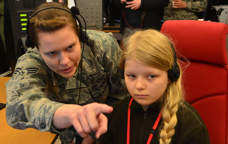 U.S. Air Force Senior Airman Jessica Mefford, 871st Air Expeditionary Squadron, shows Arna Tryggvadóttir, Pilot for a Day participant, how to operate systems at the Control and Reporting Center during the program at Keflavik International Airport, Iceland, May 13, 2015. As part of the program, both children toured the CRC and participated in a simulated mission. (U.S. Air Force photo by 2nd Lt. Meredith Mulvihill/Released)
