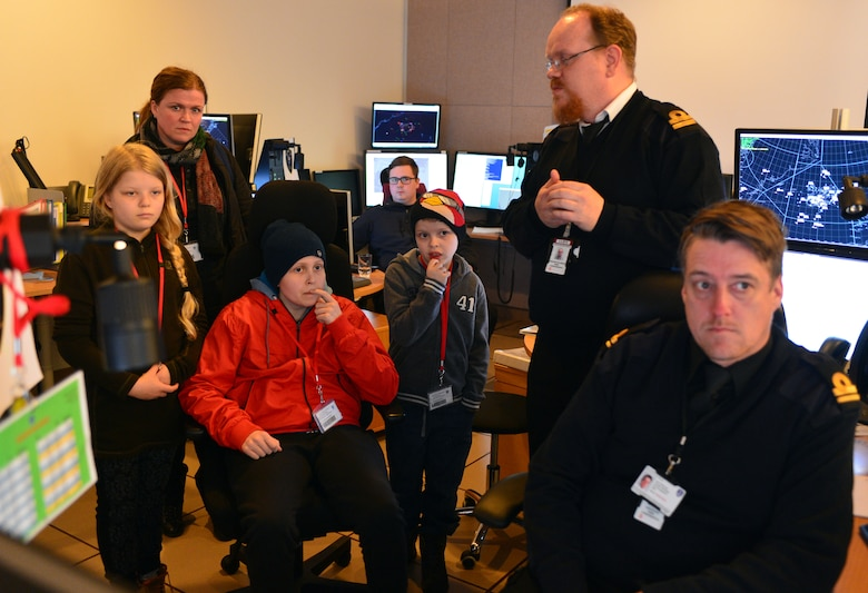 Gunnar Guðlaugsson, Arna Tryggvadóttir and their families listen to briefings by Icelandic Coast Guard and U.S. Air Force personnel at the Control and Reporting Center during the 871st Air Expeditionary Squadron Pilot for a Day program at Keflavik International Airport, Iceland, May 13, 2015. As part of the program, both children toured the CRC and participated in a simulated mission. (U.S. Air Force photo by 2nd Lt. Meredith Mulvihill/Released)