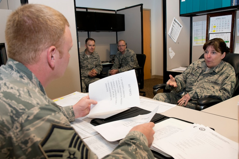 Master Sgt. Roberta Gossard, a maintenance management analyst with the 167th Airlift Wing's Maintenance Operations Flight, explains the basics of the data integrity program that is managed by maintenance analysts to Master Sgt. Justin Walther, a member of the Wing Inspection Team. As Walther interviewed Gossard during the MOF inspection, Maj. Jason G. Hughes and Senior Master Sgt. John P. Pflugradt, left to right in background, observe. Hughes and Pflugradt are members of the Air Mobility Command's Inspector General's Inspections Division. This is the first time an AMC's IG team has paid a visit to the Martinsburg wing and observed a unit inspection since the implementation here of the Air Force Inspection System (AFIS) construct. (Air National Guard photo by Staff Sgt. Sherree Grebenstein/Released)