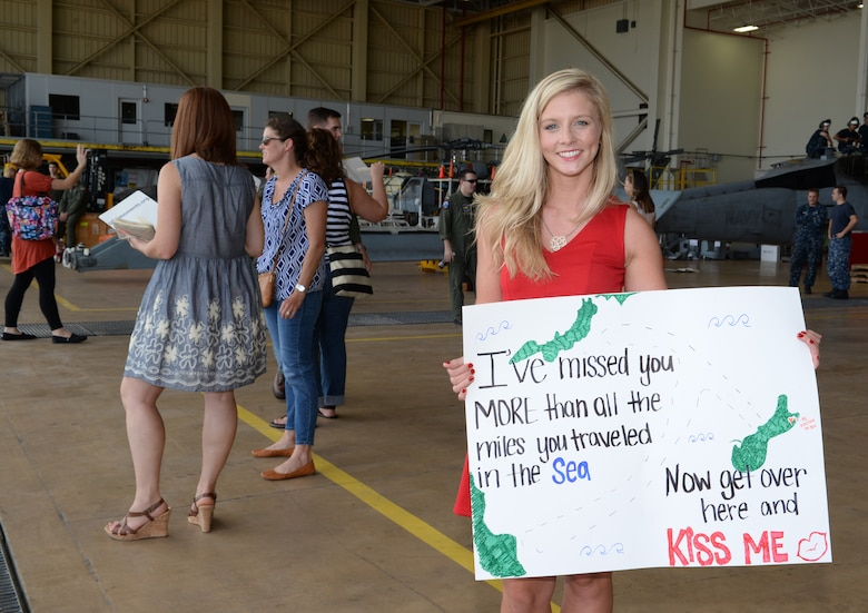 A spouse poses with sign before her husband arrives after five-month deployment May 11, 2015, at Andersen Air Force Base, Guam. While deployed, the members of Helicopter Sea Combat Squadron 25 integrated three MH-60S helicopters with the Air Combat Element during amphibious integration training and certification exercise, and Korea Marine Exchange Program. (U.S. Air Force photo by Senior Airman Amanda Morris/Released)