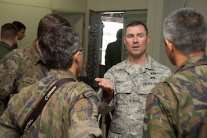 Tech Sgt. Daniel Foret, 571st Mobility Support Advisory Squadron survival, evasion, resistance and escape specialists, speaks with members of the Brazilian air force after a presentation on May 11, 2015 in Campo Grande, Brazil. Foret spoke and explained the importance of SERE specialists and how they can be utilized to train forces. (U.S. Air Force photo by Staff Sgt. Adam Grant/Released)