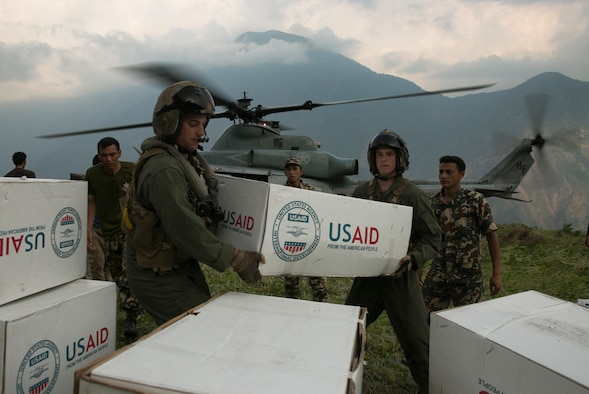 U.S. Marines and Nepalese soldiers unload tarps off of a UH-1Y Huey at Orang, Nepal, during Operation Sahayogi Haat, May 19, 2015. Joint Task Force 505 is drawing down its earthquake relief operations as the Nepalese government and international aid agencies have postured for long-term recovery and reconstruction efforts. Nepal announced its transition from relief operations to the recovery phase of disaster response May 19. (U.S. Marine Corps photo/Cpl. Isaac Ibarra)