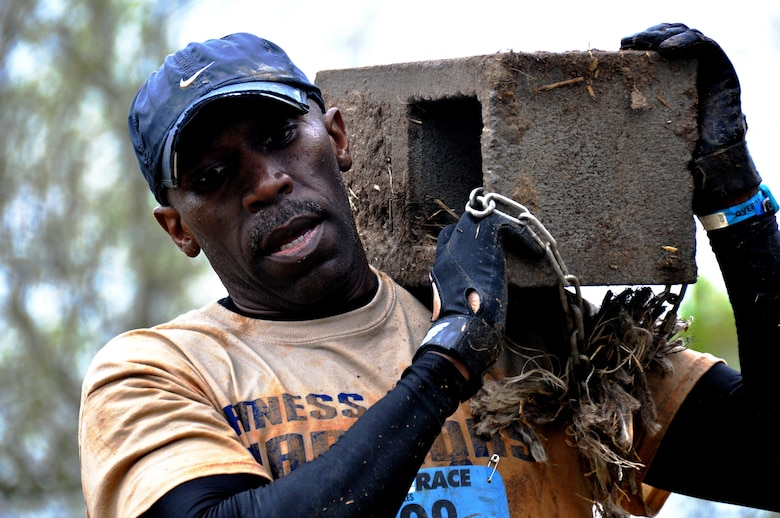 Senior Master Sgt. Eric Jones, 94th Logistics Readiness Squadron, carries a masonry brick down a hill during the Georgia Spring 2015 Savage Race in Dallas, Ga., April 18, 2015. The Savage Race is an Air Force Reserve sponsored obstacle course that challenges participants in more than 20 different trials over the course of five miles. (U.S. Air Force photo/Senior Airman Daniel Phelps)