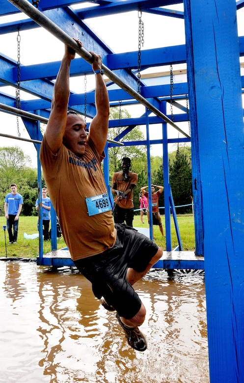Tech. Sgt. Randy Estrella, 94th Logistics Readiness Squadron vehicle maintainer, shimmies across bars over a pool of water during the Georgia Spring 2015 Savage Race in Dallas, Ga., April 18, 2015. The Savage Race is an Air Force Reserve sponsored obstacle course that challenges participants in more than 20 different trials over the course of five miles. (U.S. Air Force photo/Senior Airman Daniel Phelps)
