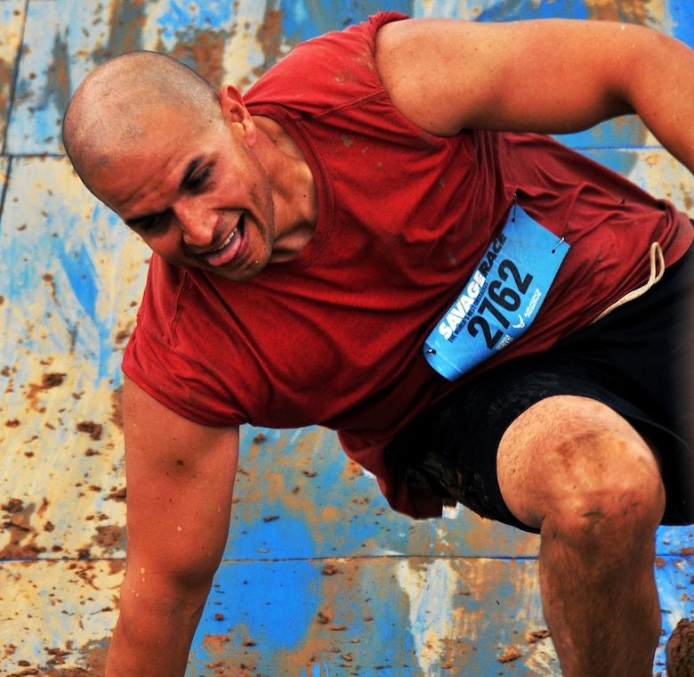 Staff Sgt. Luis Pluguez, 94th Aeromedical Staging Squadron, slides down a wall after a failed attempt at climbing the Colossus during the Georgia Spring 2015 Savage Race in Dallas, Ga., April 18, 2015. The Colossus was a giant 43-foot wall and one of the hardest obstacles in the course. Adding to the difficulty of it being one of the final obstacles, runners had to sprint up the barrier after they'd already sledged through more than four miles in the mud, before grabbing a rope. They would then pull themselves up to the top of the fortification. The Savage Race is an Air Force Reserve sponsored obstacle course that challenges participants in more than 20 different trials over the course of five miles. (U.S. Air Force photo/Senior Airman Daniel Phelps)