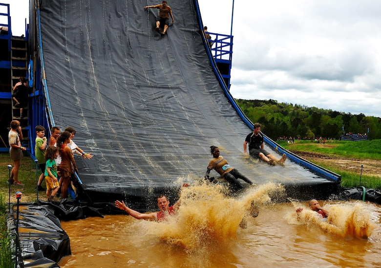 Members of Dobbins Air Reserve Base slide into a pool of water after making it to the top of the Colossus during the Georgia Spring 2015 Savage Race in Dallas, Ga., April 18, 2015. The Colossus was a giant 43-foot wall and one of the hardest obstacles in the course. Adding to the difficulty of it being one of the final obstacles, runners had to sprint up the barrier after they'd already sledged through more than four miles in the mud, before grabbing a rope. They would then pull themselves up to the top of the fortification. The Savage Race is an Air Force Reserve sponsored obstacle course that challenges participants in more than 20 different trials over the course of five miles. (U.S. Air Force photo/Senior Airman Daniel Phelps)
