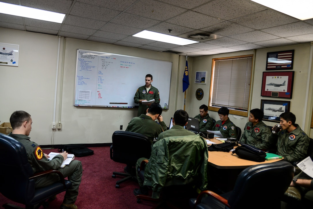 36th Fighter Squadron and Republic of Korea air force pilots have a pre-flight briefing during Buddy Wing 15-3 March 24, 2015, at Osan Air Base, ROK. The program places both ROKAF and U.S. Air Force pilots in the same briefings and flying rules that the host unit flies under. (U.S. Air Force photo by Senior Airman Matthew Lancaster)