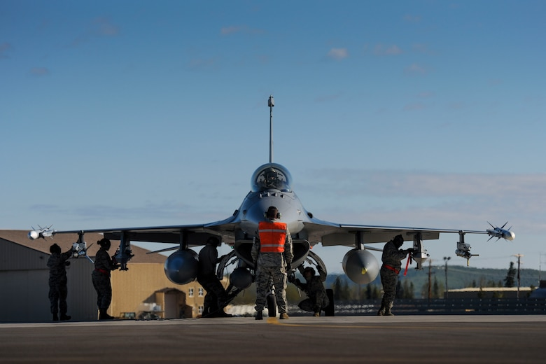 Tech. Sgt. Mark Fox stands face-to-face with an F-16 Fighting Falcon as maintenance personnel make last-minute checks before take off at Eielson Air Force Base, Tuesday, May 12, 2015 during Red Flag-Alaska 15-2. (U.S. Air National Guard photo by Capt. Nathan Wallin)